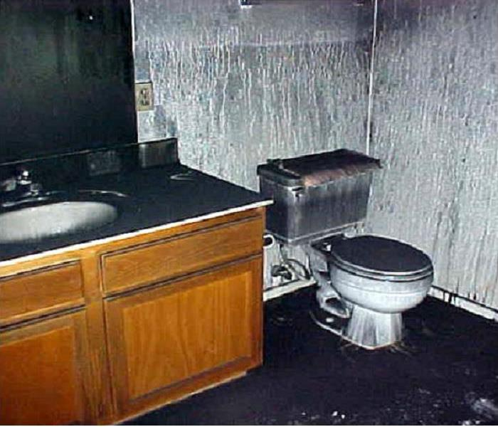 Smoke damage to a bathroom, the walls and toilet have gray soot all over them.